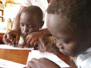 9歳にして生まれて初めて鉛筆を握る子たち(右Lamunu Lucky)。持ち方から教えます。〇や△、線を引くのも一苦労~!