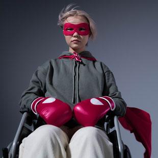 Mädchen mit Boxhandschuhen und Cape im Rollstuhl