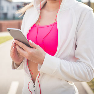 Joggerin blickt auf ihr Smartphone
