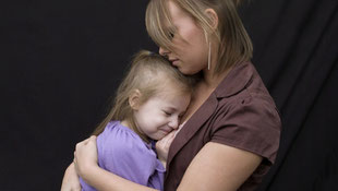 Mutter hält weinendes Kind im Arm