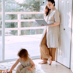 Frau steht mit Notebook neben spielender Tochter