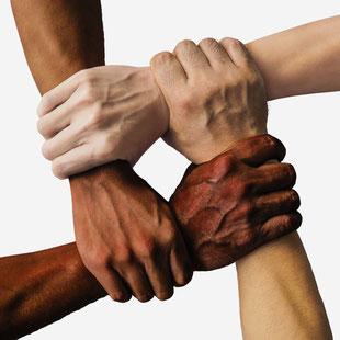 Vier Hände halten einander kreuzweise