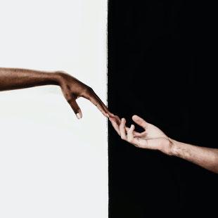 Eine farbige und eine hellhäutige Hand reichen einander