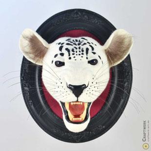 Gefilzter weißer Leopardenkopf mit schwarzen Flecken, offenen Maul und gefletschten Zähnen