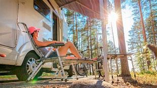 Campingurlaub vom Feinsten: Frau sitzt entspannt auf einem Campingstuhl vor ihrem Wohnwagen im Wald. Die Sonne scheint zwischen die Bäume.