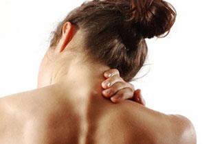 Frau greift sich wegen Schmerzen an den Nacken