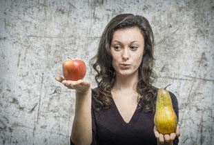 Frau prüft einen Apfel und eine Birne