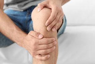 Mann hält sich wegen Schmerzen das Kniegelenk