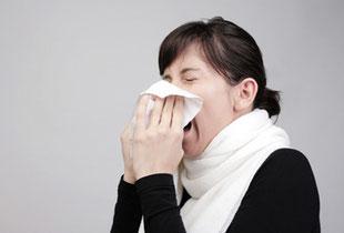 Frau mit akutem Infekt putzt sich die Nase