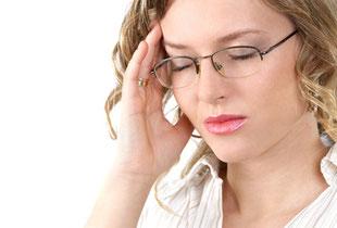 Frau greift sich wegen Migräneschmerzen an die Schläfe