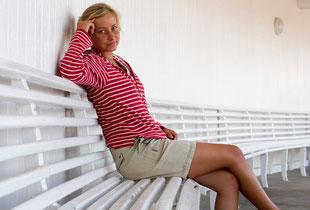 Junge Krebspatientin auf einer Bank sitzend