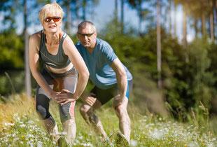 2 Personen beim Dehnen vor einem Lauftraining im Wald