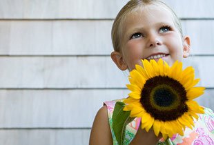 Kind mit einer Sonnenblume vor Hauswand