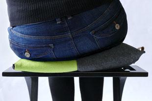 dynamisches Sitzen mit dem grau/grünem Flowmo Pad nach links geneigt