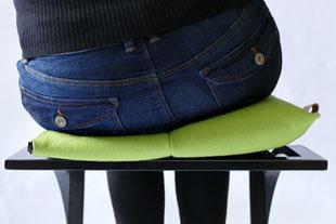 dynamisches Sitzen mit dem hellgrünem Flowmo Pad nach links geneigt