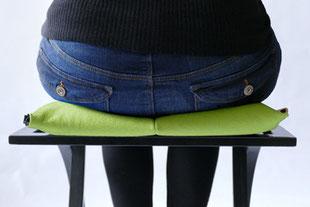 dynamisches Sitzen mit dem hellgrünem Flowmo Pad mittig aufrecht