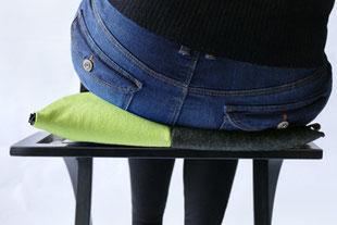 dynamisches Sitzen mit dem grau/grünem Flowmo Pad nach rechts geneigt