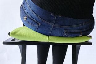 dynamisches Sitzen mit dem hellgrünem Flowmo Pad nach rechts geneigt