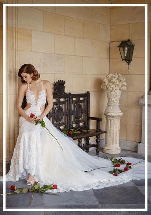 Braut im Brautkleid sitzend mit roter Rose in romantischer Kulisse