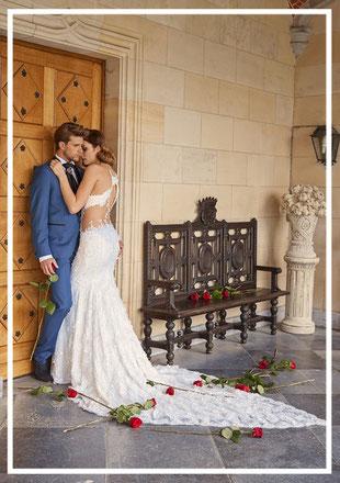 Braut im Brautkleid mit Schleppe und Bräutigam im Anzug stehend vor einem großen Tor