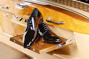 schwarze glänzende Schuhe auf Autoablage