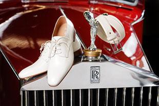 Auf einem roten Rolls Royce liegend: Schuhe und Gürtel in weiß