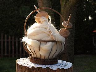 Spinnen  Ein Korb voll Wolle wartet darauf, dass er von den bereitliegenden Handspindeln zu Fäden verarbeitet wird.