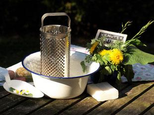 Seife selber machen. In einer Emailleschüssel befindet sich eine Reibe, auf der Seife fein geraspelt werden soll.