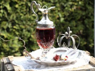 Heilwein In einer Glaskaraffe mit drachenförmigem Griff leuchtet eine rubinrote Flüssigkeit.