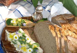 Frisches Brot mit Butter bestrichen und mit Wildkräutern bestreut.