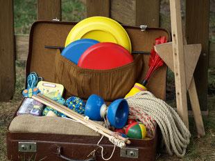 Ein Koffer voller Spielabenteuer: Bälle, Springseile, Stelzen, Jutesäcke versprechen eine lustige Olympiade für Kinder und Erwachsene.