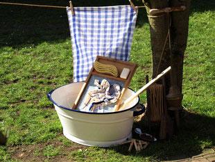 Nostalgisch Wäsche waschen. Eine Emaillewanne mit Waschbrett, Wäschestampfer, Seife, Leinentuch und Wäscheleine stehen für die nostalgische Waschaktion bereit.