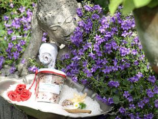 Badesalz selbst kreiert In einem blauen Blütenmeer liegt ein Buddha, der auf eine silberne Schale voll Badesalz mit Blüten schaut.