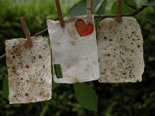 Selbst geschöpftes Papier mit tollen Mustern hängt zum Trocknen an einem Kirschbaumzweig.