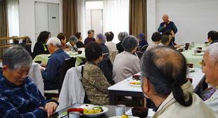 高齢者食事会で主催者のあいさつを聞く高齢者たち