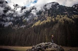Junger Mann auf einem Felsen vor einer Bergkulisse im Hintergrund Nebel und Wald festgehalten von der Familien Fotografin Monkeyjolie in Graubünden