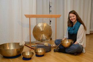 Martina Schlecht, Klangpädagogin sitzend in ihrem Klangraum. Neben ihr verschiedene Klangschalen und ein Fen-Gong.