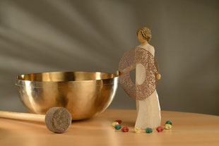 Eine Klangschale steht auf dem Tisch. Daneben eine Willow Tree Figur ,Wellcome Here