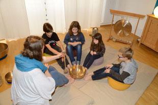 Die Klangpädagogin sitzt mit 4 Kindern am Boden im Sitzkreis. In der Mitte steht eine gr. Beckenschale und alle strecken ihre Füße in die Mitte hin zur Klangschale