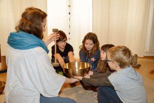 Die Klangpädagogin sitzt mit 4 Kindern in einem Sitzkreis am Bodern. Alle strecken Ihre Hände in die Mitte und auf den Handflächen steht eine gr. Beckenschale