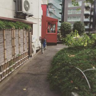 小道に入りますと前方に赤い外壁の飲食店が見えます。お店の脇にビル入口があります。