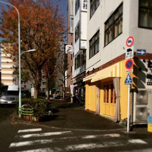 地上に出ましたらそのまま直進です。黄色い外壁の飲食店やセブンイレブンが見えます。