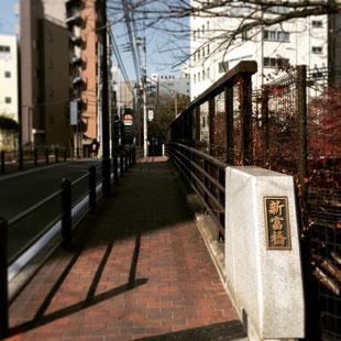 信号を左折してから少し直進しますと首都高の上にかかる新富橋が見えてきますので橋をお渡り下さい。