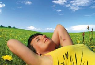 Frau liegt mit gelben T-Shirt auf einer Wiese