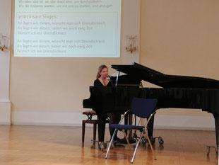 Das Foto zeigt eine junge Frau am Klavier auf der Bühne. Im Hintergrund eine Projektion mit dem Text gemeinsam Singen Refrain von An Tagen wie diesen, wünscht man sich Unendlichkeit.
