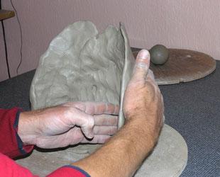 Zwei Hände formen das Material Ton zu einer Wand