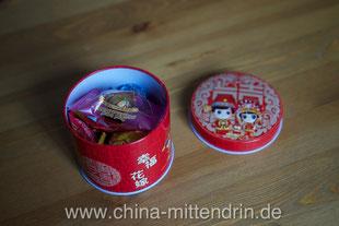 Ein Blick in die Geschenkdose: Bonbons und getrocknetes Obst. Ideal zum Weiterverschenken - wenn da nicht die typische Hochzeitsdekoration auf der Dose wäre ...
