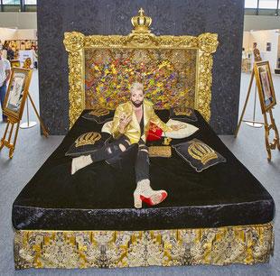 HARALD GLÖÖCKLER auf einem Boxspringbett-Unikat von Femira mit einem Kopfteil wie ein Gemälde. Das von ihm selbst gestaltete Bett feiert auf der EUNIQUE eine exklusive Preview.