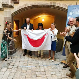 Céline Ripoll, Française habitante de l'Île de Pâques, remet à Monique Bultel Herment, conseillère régionale et aux autorité locales, le drapeau de l'Île de Pâques