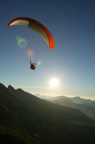 Ein Gleitschirm fliegt bei Sonnenuntergang